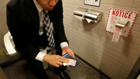 Man demonstrates a toilet roll for wiping smartphones, installed by Japanese mobile phone company NTT Docomo, in a high-tech bathroom equipped with bidet and heated seat at Narita international airport in Narita